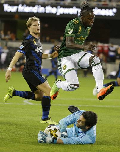 San Jose Earthquakes goalkeeper Andrew Tarbell, bottom, grabs the ball under Portland Timbers forward Darren Mattocks during the second half of an MLS soccer match in San Jose, Calif., Saturday, Sept. 30, 2017.