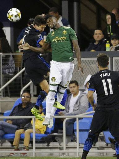 Portland Timbers forward Dairon Asprilla, center, jumps for the ball next to San Jose Earthquakes midfielder Shea Salinas during the first half of an MLS soccer match in San Jose, Calif., Saturday, Sept. 30, 2017.