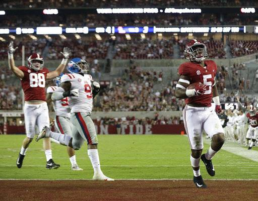 Alabama tight end Ronnie Clark scores a touchdown against Mississippi defensive tackle Breeland Speaks during the second half of an NCAA college football game, Saturday, Sept. 30, 2017, in Tuscaloosa, Ala.
