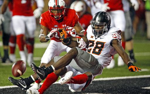 Texas Tech's Octavious Morgan, bottom, tackles Oklahoma State's James Washington (28) as he misses the pass during the NCAA college football game Saturday, Sept. 30, 2017, in Lubbock, Texas. (Brad Tollefson/Lubbock Avalanche-Journal via AP)