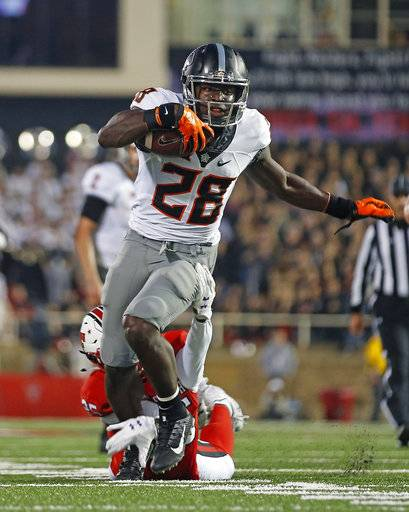 Oklahoma State's James Washington (28) runs the ball down the field during the NCAA college football game against Texas Tech, Saturday, Sept. 30, 2017, in Lubbock, Texas. (Brad Tollefson/Lubbock Avalanche-Journal via AP)