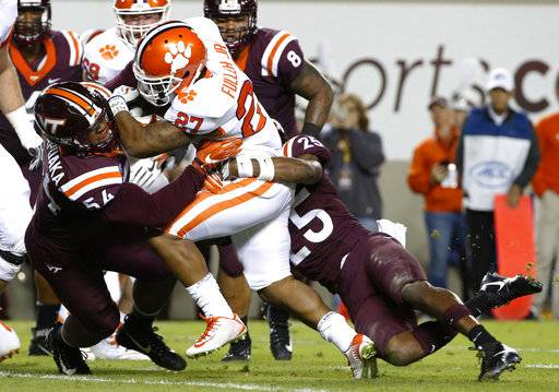 Clemson running back C.J. Fuller (27) powers in for a touchdown as Virginia Tech linebacker Andrew Motuapuaka (54) and safety Terrell Edmunds try to make the stop during the first half of an NCAA college football game in Blacksburg, Va., Saturday, Sept. 30, 2017.