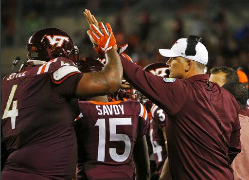 Virginia Tech head coach Justin Fuente welcomes defensive tackle Tim Settle (4) back to the bench after a stop during the first half of an NCAA college football game against Clemson in Blacksburg, Va., Saturday, Sept. 30, 2017.