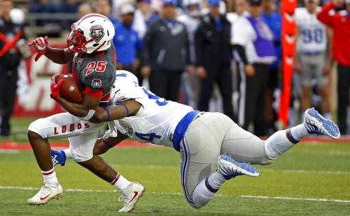New Mexico running back Tyrone Owens (25) is sacked by Air Force defensive tackle Jordan Jackson during the first half of an NCAA college football game in Albuquerque, N.M., Saturday, Sep. 30, 2017.