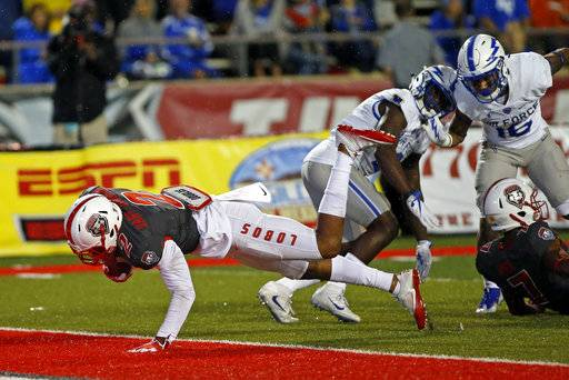 New Mexico wide receiver Delane Hart-Johnson (2) dives into the end zone past Air Force defensive backs Robert Bullard (16) and Marquis Griffin (2) during the second half of an NCAA college football game in Albuquerque, N.M., Saturday, Sept. 30, 2017. New Mexico won 56-38.