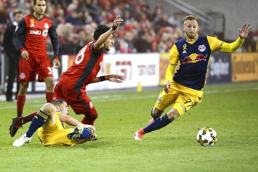 Toronto FC's Marky Delgado (18) chases after New York Red Bulls' Daniel Royer, right, as he jumps over Red Bulls' Connor Lade during the second half of an MLS soccer game, Saturday, Sept. 30, 2017, in Toronto. (Jon Blacker/The Canadian Press via AP)