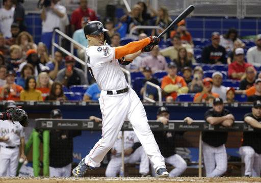 Miami Marlins' Giancarlo Stanton hits a RBI single to score Miguel Rojas during the fifth inning of a baseball game against the Atlanta Braves, Saturday, Sept. 30, 2017, in Miami.