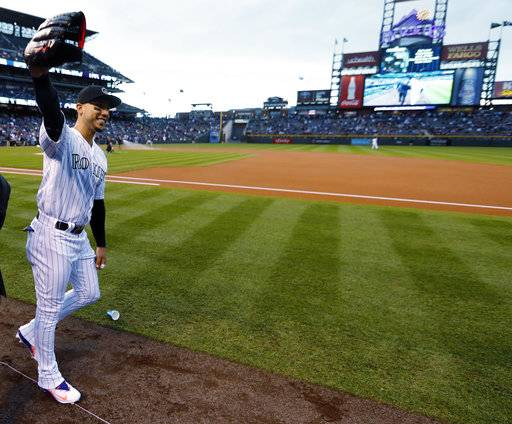 Colorado Rockies right fielder Carlos Gonzalez acknowledges fans as he takes the field to face the Los Angeles Dodgers in the first inning of a baseball game Saturday, Sept. 30, 2017, in Denver.