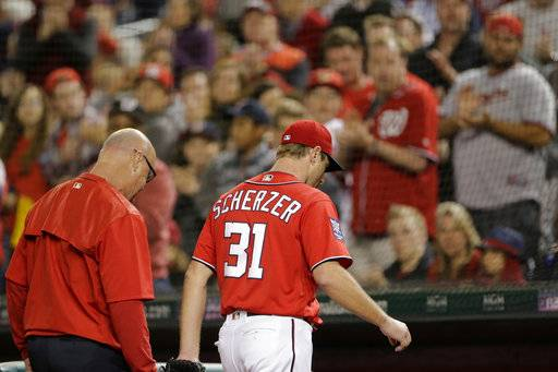 Washington Nationals starting pitcher Max Scherzer, right, walks to the dugout with Director of Athletic Training Paul Lessard, left, after being pulled in the fourth inning of a baseball game against the Pittsburgh Pirates, Saturday, Sept. 30, 2017, in Washington.