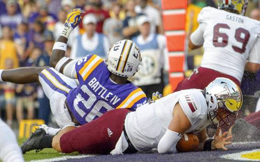 Troy quarterback Brandon Silvers (12) scores a touchdown against LSU safety John Battle (26) in the first half of an NCAA college football game in Baton Rouge, La., Saturday, Sept. 30, 2017.