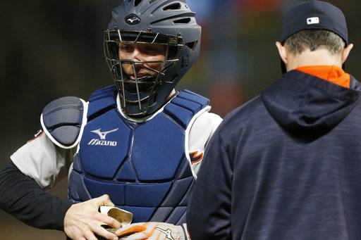 Detroit Tigers' Andrew Romine, left, is pulled as catcher during the baseball game against the Minnesota Twins Saturday, Sept. 30, 2017, in Minneapolis. Romine joined a select few players in history by playing in all nine positions during the game. The Tigers won 3-2.