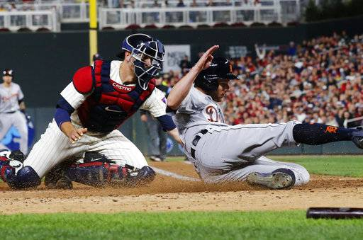Minnesota Twins catcher Jason Castro tags out Detroit Tigers' Andrew Romine, after he tried to score from third on a single by Nicholas Castellanos during the fifth inning of a baseball game Saturday, Sept. 30, 2017, in Minneapolis.