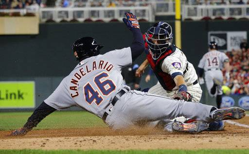 Detroit Tigers' Jaime Candelario, left, slides past Minnesota Twins' catcher Jason Castro to score after Castro dropped the ball during the fifth inning of a baseball game Saturday, Sept. 30, 2017, in Minneapolis.