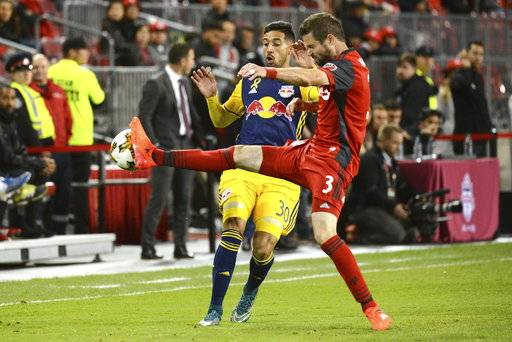 Toronto FC's Drew Moor, right, strips the ball from New York Red Bulls' Gonzalo Veron during the first half of an MLS soccer game, Saturday, Sept. 30, 2017, in Toronto. (Jon Blacker/The Canadian Press via AP)