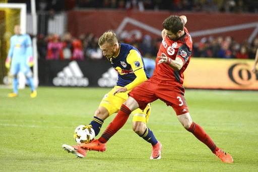 Toronto FC's Drew Moor, right, fights for the ball against New York Red Bulls' Arun Basuljevic during the first half of an MLS soccer game, Saturday, Sept. 30, 2017, in Toronto. (Jon Blacker/The Canadian Press via AP)