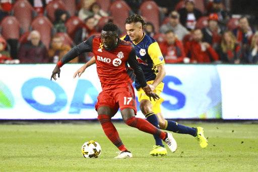 Toronto FC's Jozy Altidore, left, takes possession of the ball ahead of New York Red Bulls' Aaron Long during the first half of an MLS soccer game, Saturday, Sept. 30, 2017, in Toronto. (Jon Blacker/The Canadian Press via AP)
