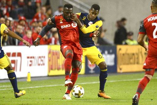 Toronto FC's Jozy Altidore, left, fights for the ball against New York Red Bulls' Michael Murillo during the first half of an MLS soccer game, Saturday, Sept. 30, 2017, in Toronto. (Jon Blacker/The Canadian Press via AP)