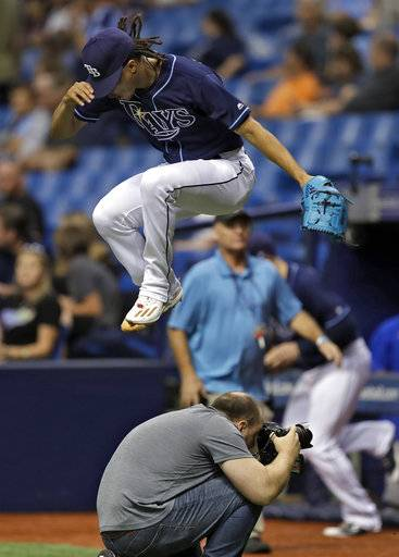Tampa Bay Rays starting pitcher Chris Archer leaps over Tampa Bay Times photographer Will Vragovic as he takes the field before a baseball game against the Baltimore Orioles, Saturday, Sept. 30, 2017, in St. Petersburg, Fla.