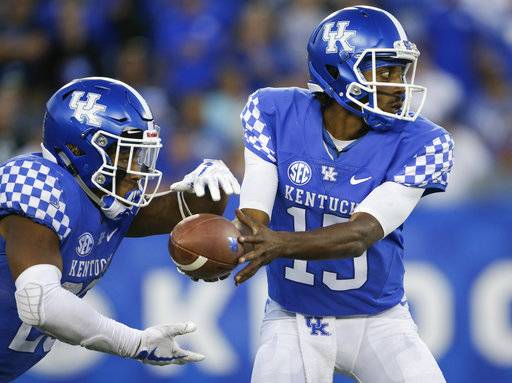 Kentucky quarterback Stephen Johnson hands off the ball to running back Benny Snell Jr. during the second half of an NCAA college football game against Eastern Michigan Saturday, Sept. 30, 2017, in Lexington, Ky. Kentucky won the game 24-20.