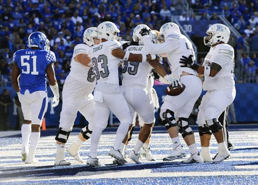 Eastern Michigan wide receiver John Niupalau (89) is mobbed by team mates after he scored a touchdown during the first half of an NCAA college football game against Kentucky Saturday, Sept. 30, 2017, in Lexington, Ky.