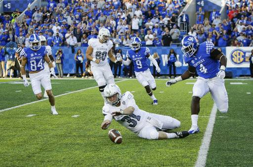 Eastern Michigan punter Jake Julien dives on a loose ball after his punt was blocked resulting in Kentucky's possession and subsequent touchdown during the second half of an NCAA college football game Saturday, Sept. 30, 2017, in Lexington, Ky. Kentucky won the game 24-20.