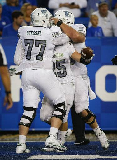 Eastern Michigan running back Ian Eriksen is mobbed by teammates after he scored a touchdown during the second half of an NCAA college football game against Kentucky Saturday, Sept. 30, 2017, in Lexington, Ky. Kentucky won the game 24-20.