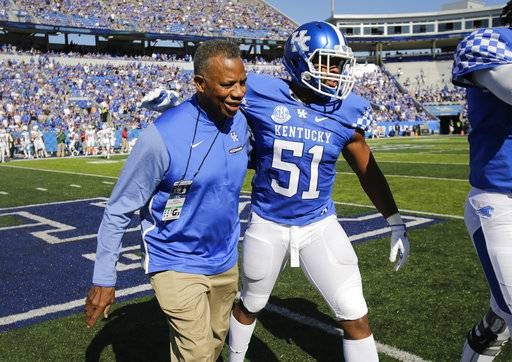 Linebacker Courtney Love, one of Kentucky's team captains, walks off the field with honorary team captain Nate Northington after the coin toss before the first half of an NCAA college football game against Eastern Michigan Saturday, Sept. 30, 2017, in Lexington, Ky. Kentucky honored Northington today, 50 years after signing him as the first African-American to play football in the SEC.