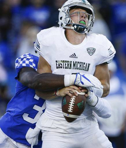 Eastern Michigan quarterback Brogan Roback is sacked by Kentucky defensive end Denzil Ware during the second half of an NCAA college football game Saturday, Sept. 30, 2017, in Lexington, Ky. Kentucky won the game 24-20.