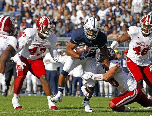 Penn State's Saquon Barkley (26) is brought down by Indiana's Chase Dutra (30) during the first half of an NCAA college football game in State College, Pa., Saturday, Sept. 30, 2017.