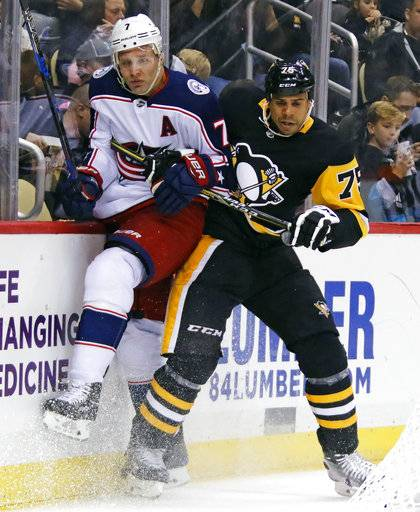 Pittsburgh Penguins' Ryan Reaves (75) checks Columbus Blue Jackets' John Mitchell (7) into the boards during the second period of a NHL preseason hockey game in Pittsburgh, Saturday, Sept. 30, 2017.