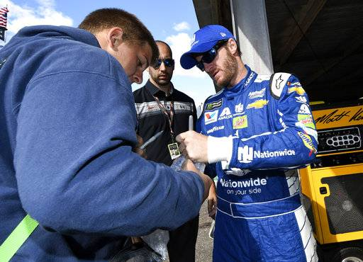 Dale Earnhardt Jr., right, signs for a fan before practice for the NASCAR Cup series auto race, Saturday, Sept. 30, 2017, at Dover International Speedway in Dover, Del.
