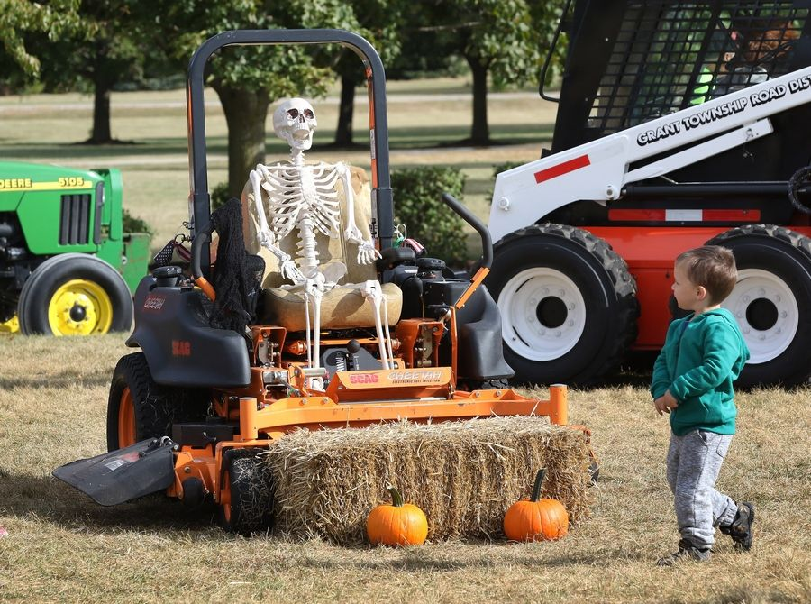 Landon Fick, 3, of Ingleside walks by a skeleton in a power mower Sunday during the Fall Festival at Grant Township. The event featured big construction vehicles, pumpkin-carving contest and pie-eating contests, a crafts fair and games for kids.