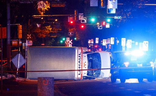 A U-Haul truck rests on its side after a high-speed chase with police in Edmonton Alta, on Saturday Sept. 30, 2017.  Police say the U-Haul intentionally swerved at pedestrians at crosswalks throughout the chase. (Jason Franson/The Canadian Press via AP)