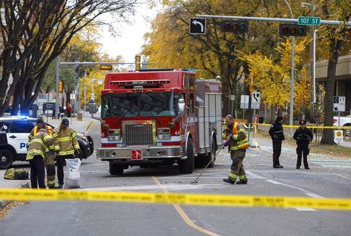 Crews clean up the scene where a cube van ran into pedestrians and later flipped over while being pursued by police, in Edmonton Alta, on Sunday Oct. 1, 2017. The car and knife attack on a police officer outside a football game and a high-speed chase of a moving van that left four people injured appear to be the work of a single suspected terrorist, Canadian authorities said Sunday. (Jason Franson/The Canadian Press via AP)