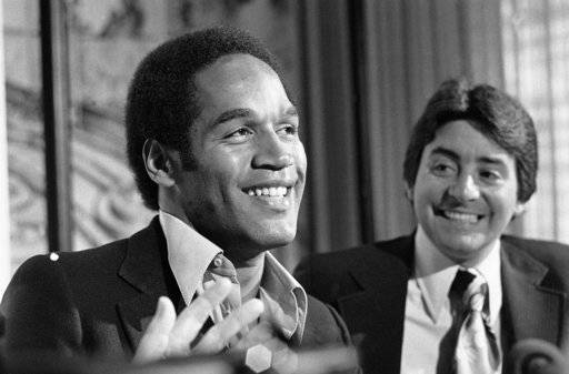FILE - In this March 24, 1978, file photo, a jubilant O.J. Simpson met the press in San Francisco where the 49ers announced that Simpson had been traded to them from the Buffalo Bills. O.J. said he was ecstatic about the opportunity to play in the city where he was born. At right is San Francisco 49ers owner, Edward DeBartolo Jr. O.J. Simpson's release from a Nevada prison turns another page in one of the most dramatic falls from grace in American pop culture history. A beloved college and pro football hero in the 1960s and '70s, Simpson went on to become a movie star, sports commentator and TV pitchman in the years before the 1994 killings of his ex-wife and her friend in Los Angeles. A Nevada prison official said early Sunday, Oct. 1, 2017, O.J. Simpson, the former football legend and Hollywood star, has been released from a Nevada prison in Lovelock after serving nine years for armed robbery.