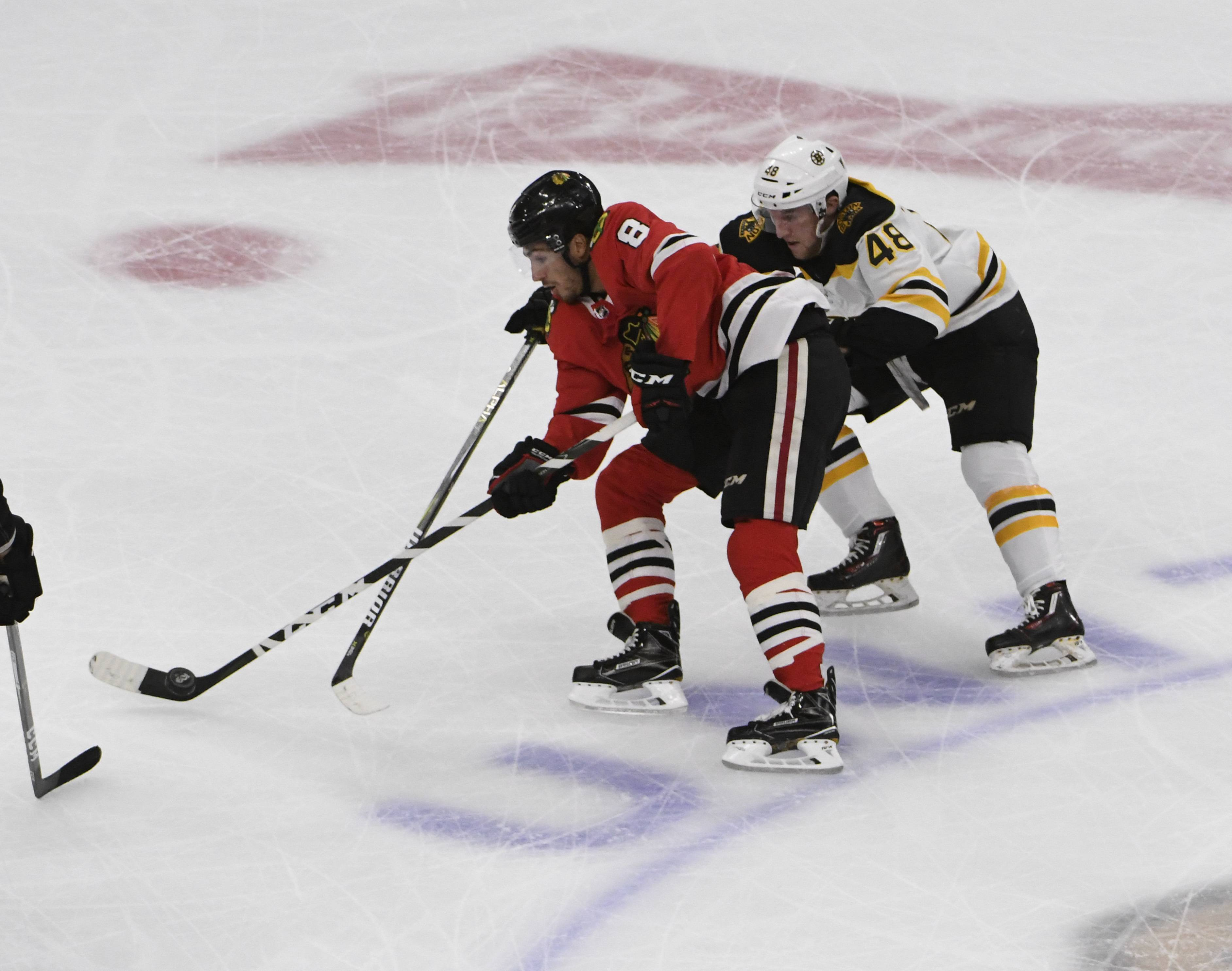 Boston Bruins defenseman Matt Grzelcyk (48) and Chicago Blackhawks center Nick Schmaltz (8) go for the puck in the first period of a preseason NHL hockey game Saturday, Sept. 30, 2017, in Chicago.