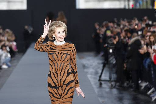 Actress Jane Fonda gestures a peace sign as she wears a creation for L'Oreal Spring/Summer 2018 ready-to-wear fashion collection presented in Paris, Sunday, Oct .1, 2017.