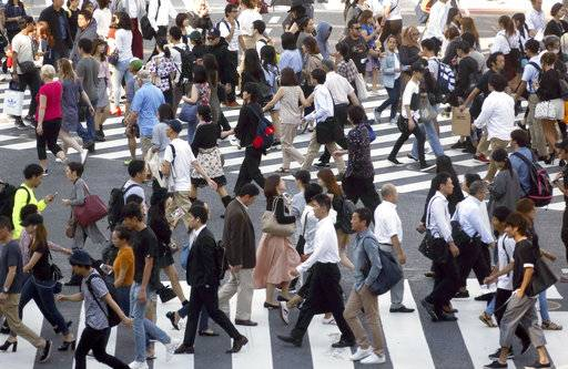 In this Sept. 29, 2017 photo, people cross streets at Tokyo's shopping and entertainment district of Shibuya in Tokyo. The Bank of Japan's quarterly survey shows an improved outlook for the world's third largest economy. The survey released Monday, Oct. 2, 2017,  indicated growing shortages of factory capacity that could drive manufacturing investment to help drive growth. However the longer term prospects were less upbeat, and overall growth looks set to remain at current steady but lackluster levels.