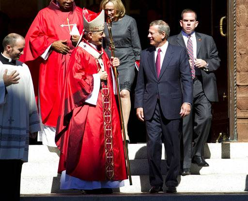 Cardinal Donald Wuerl, Archbishop of Washington, speaks with U.S. Supreme Court Chief Justice John Roberts as they leave St. Mathews Cathedral after the Red Mass in Washington on Sunday, Oct. 1, 2017. The Supreme Court's new term starts Monday, Oct. 2.