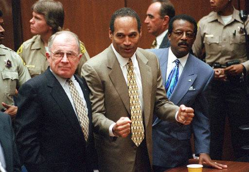 FILE - In this Oct. 3, 1995 file photo, O.J. Simpson reacts as he is found not guilty of murdering his ex-wife Nicole Brown Simpson and her friend Ron Goldman, at the Criminal Courts Building in Los Angeles. At left is defense lawyer F. Lee Bailey and at right is defense attorney Johnnie Cochran Jr. Defense attorney Robert Shapiro is in profile behind them. On Oct. 3, 1995: Simpson is acquitted of murder. A Nevada prison official said early Sunday, Oct. 1, 2017, O.J. Simpson, the former football legend and Hollywood star, has been released from a Nevada prison in Lovelock after serving nine years for armed robbery. (Myung J. Chun/Pool Photo via AP, File)