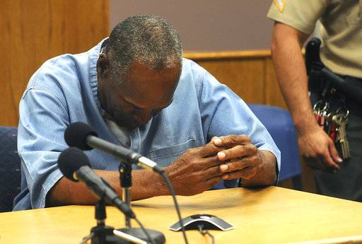 FILE - In this July 20, 2017, file photo, former NFL football star O.J. Simpson reacts after learning he was granted parole at Lovelock Correctional Center in Lovelock, Nev. Simpson was convicted in 2008 of enlisting some men he barely knew, including two who had guns, to retrieve from two sports collectibles sellers some items that Simpson said were stolen from him a decade earlier. A Nevada prison official said early Sunday, Oct. 1, 2017, O.J. Simpson, the former football legend and Hollywood star, has been released from a Nevada prison in Lovelock after serving nine years for armed robbery.  (Jason Bean/The Reno Gazette-Journal via AP, Pool, File)