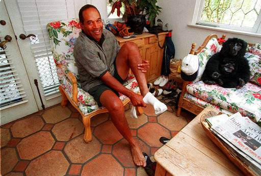 FILE - In this June 5, 1997, file photo, O.J. Simpson reacts as he puts on socks inside his home during a rare at-home interview with The Associated Press in the Brentwood section of Los Angeles. Three years and two trials after his ex-wife's slaying, O.J. says he's resigned to a future clouded by public disdain and financial ruin but is buoyed by loyal friends and the challenge of raising two children. February 1997: After a trial in a civil suit filed by the victims' families, a jury finds Simpson liable for the deaths and orders he pay survivors $33.5 million. A Nevada prison official said early Sunday, Oct. 1, 2017, O.J. Simpson, the former football legend and Hollywood star, has been released from a Nevada prison in Lovelock after serving nine years for armed robbery.