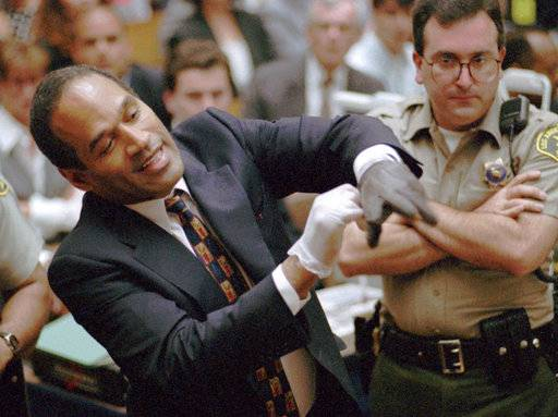 "FILE - In this June 15, 1995 file photo, O.J. Simpson, left, grimaces as he tries on one of the leather gloves prosecutors say he wore the night his ex-wife Nicole Brown Simpson and Ron Goldman were murdered in a Los Angeles courtroom. During Simpson's trial, a prosecutor asks him to put on a pair of gloves believed worn by the killer. The gloves appear too small, leading defense attorney Johnnie Cochran to famously state in his closing argument: ""If it doesn't fit, you must acquit."" A Nevada prison official said early Sunday, Oct. 1, 2017, O.J. Simpson, the former football legend and Hollywood star, has been released from a Nevada prison in Lovelock after serving nine years for armed robbery."