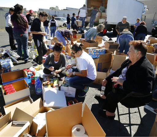 Volunteers sort collected emergency supplies for hurricane relief efforts for Puerto Rico at Chino Stars Barbershop on Mildothian Turnpike in Richmond, Va., on Sunday, Oct. 1, 2017. (Joe Mahoney/Richmond Times-Dispatch via AP)