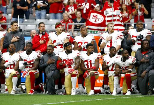 Members of the San Francisco 49ers kneel as others stand during the national anthem prior to an NFL football game against the Arizona Cardinals, Sunday, Oct. 1, 2017, in Glendale, Ariz.