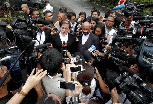 CORRECTS NAME TO NAME OF LAWYER AT LEFT - Naran Singh, center, and Hisyam Teh Poh Teik, left, lawyers for Vietnamese Doan Thi Huong, speaks to journalists at the court hearing at Shah Alam court house at Shah Alam outside Kuala Lumpur, Malaysia, Monday, Oct. 2, 2017. Two women accused of fatally poisoning the estranged half brother of North Korea's ruler pleaded not guilty as their trial began in Malaysia, nearly eight months after the brazen assassination that sparked a diplomatic standoff. They are suspected of smearing Kim Jong Nam's face with the banned VX nerve agent at a crowded airport terminal and have said they thought they were playing a harmless prank for a TV show.