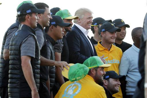 President Donald Trump poses for photos with the International Team after the final round of the Presidents Cup golf tournament at Liberty National Golf Club in Jersey City, N.J., Sunday, Oct. 1, 2017.