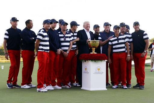 President Donald Trump, center, poses with the U.S. Team after presenting them with the winner's trophy following the final round of the Presidents Cup golf tournament at Liberty National Golf Club in Jersey City, N.J., Sunday, Oct. 1, 2017.