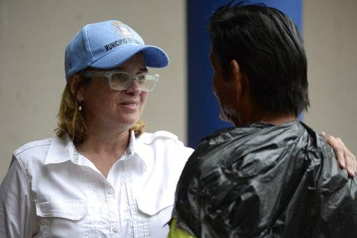 Mayor Carmen Yulin Cruz speaks with a man as she arrives at San Francisco hospital in the Rio Piedras area of San Juan, Puerto Rico, Saturday, Sept. 30, 2017, as about 35 patients are evacuated after the failure of an electrical plant.
