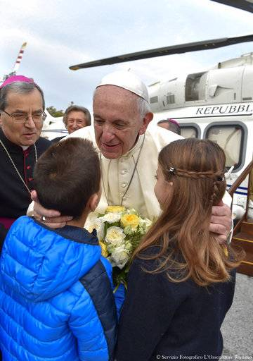 Pope Francis is greeted by two children as he arrives in Cesena, Italy, Sunday, Oct. 1, 2017. Pope Francis is in Cesena and Bologna for a one-day visit. (L'Osservatore Romano/ Pool photo via AP)